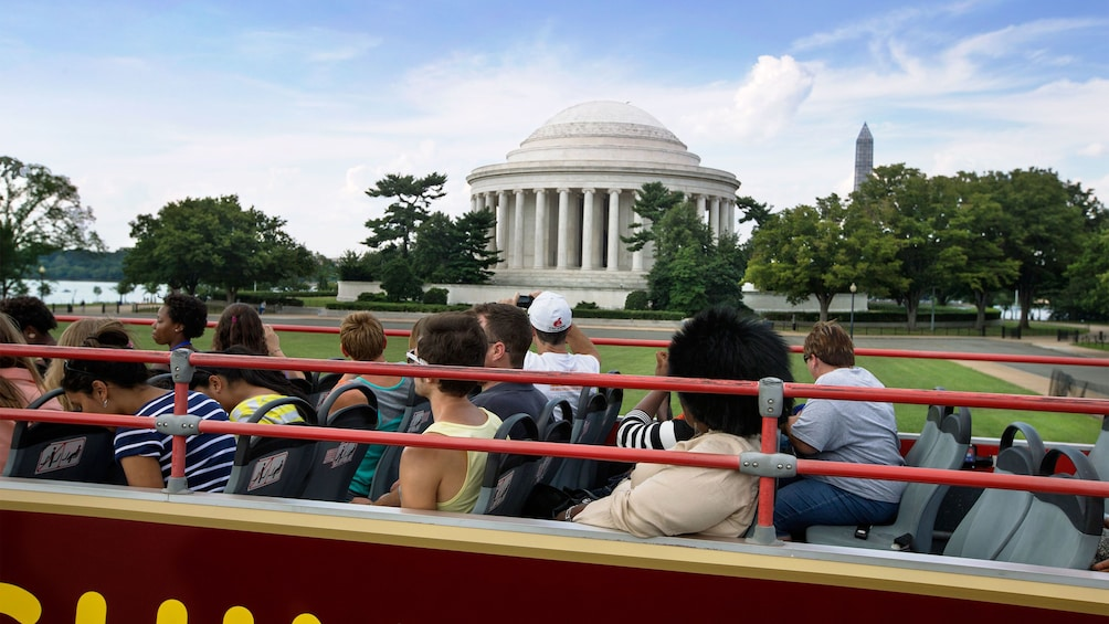 Show item 4 of 12. Double decker bus driving past the Jefferson Memorial in Washington DC