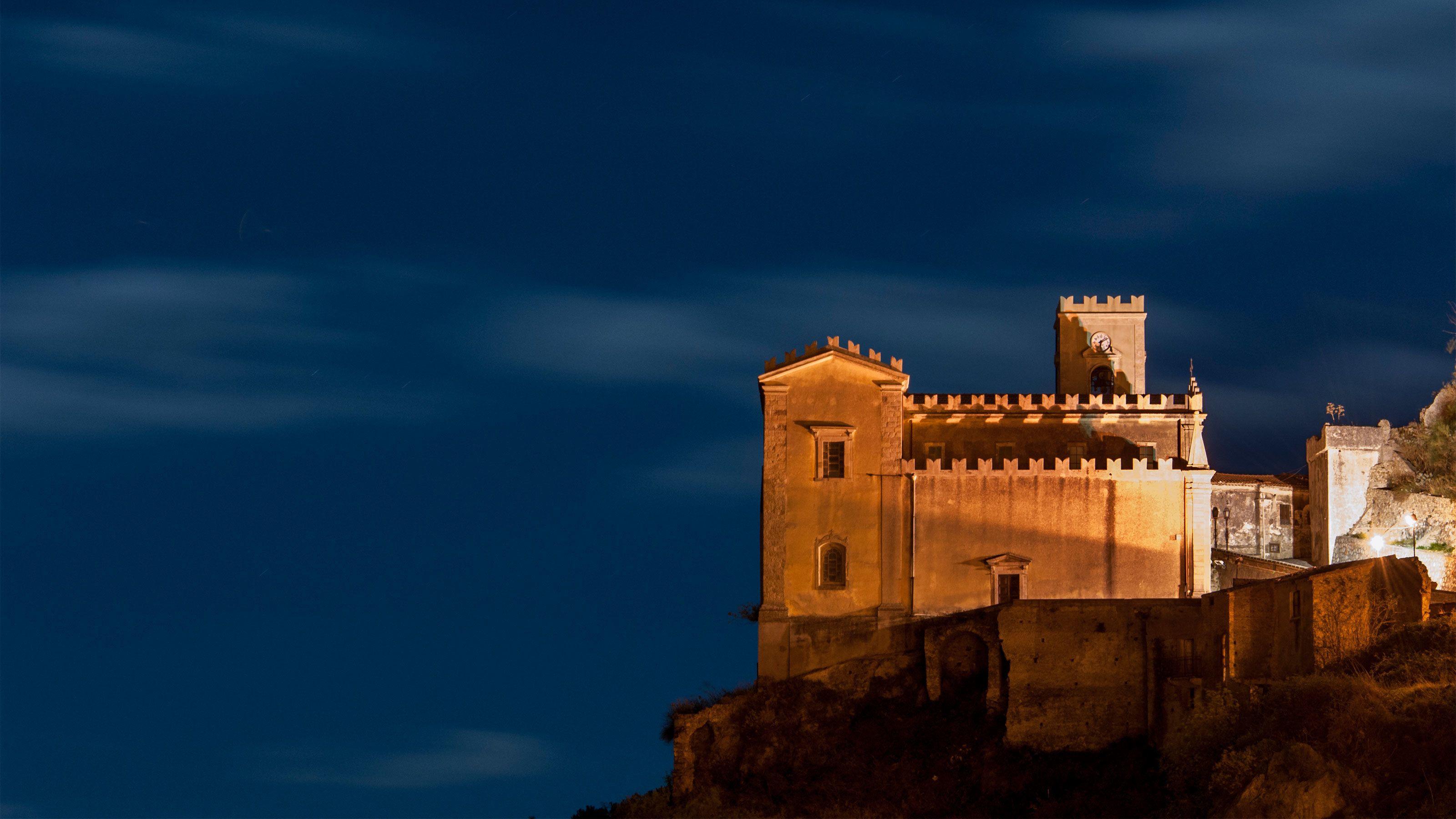 Cliffside castle at night in Taormina