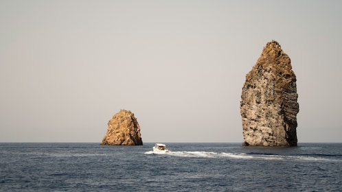 Boat next to two large rocks jutting out of the water in Lipari