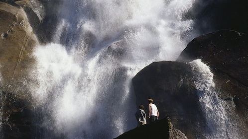 Couple at the foot of a large waterfall in Whistler