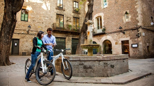 Couple on ebikes near a fountain in the Gothic Quarter of Barcelona