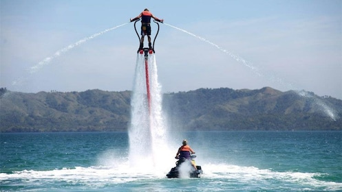Flyboarder in the air over a jetskieri in Tenerife