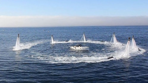 Flyboarding group form a circle in the air around a boat in Tenerife