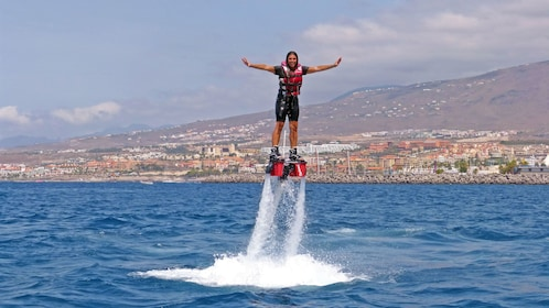 Smiling woman on flyboard over the water in Tenerife