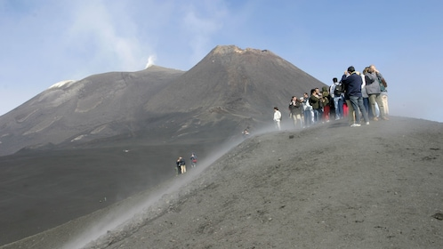 Group standing on a peak looking at Mount Etna