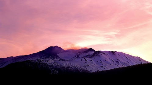 Mount Etna at sunset with a pink sky