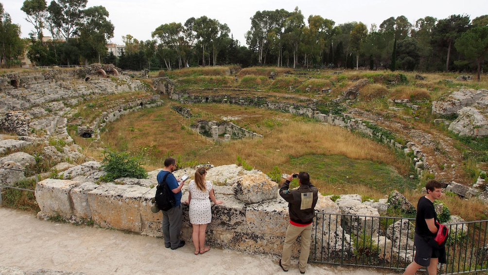 Show item 2 of 9. Tour group at the Roman ampitheater ruins in Syracuse