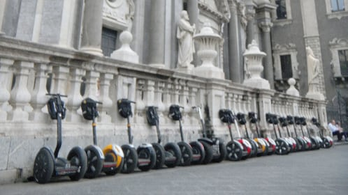 Segways lined up outside a building in Catania
