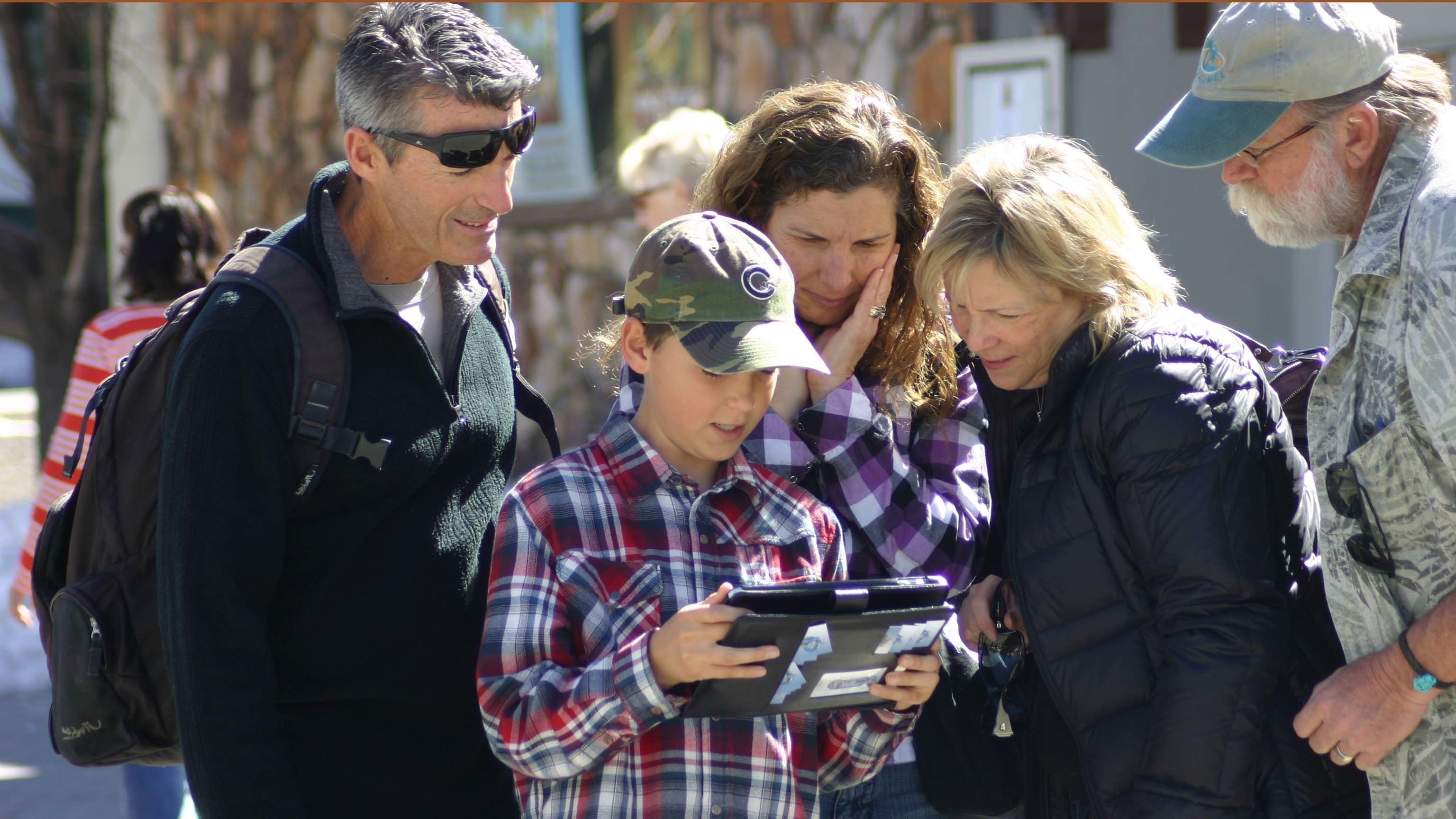 Multi-generational family looking at handheld device during a family scavenger hunt