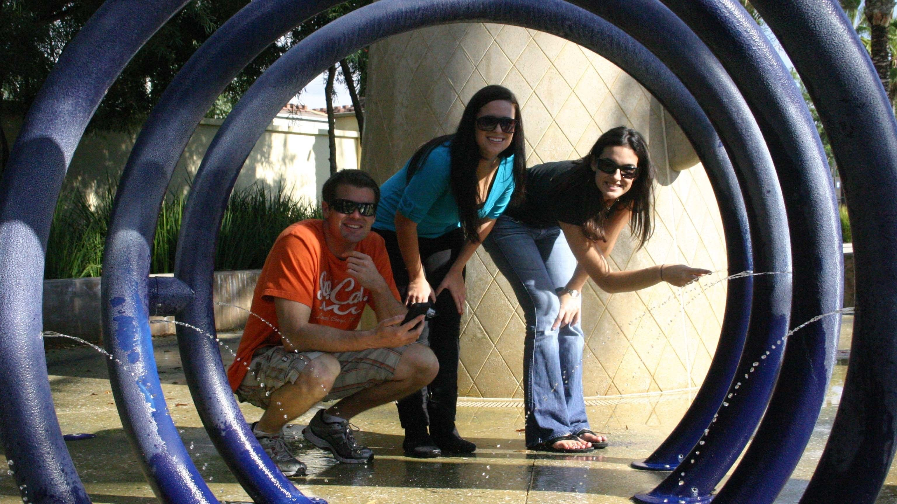 Trio of young adults framed by circular water display during a scavenger hunt