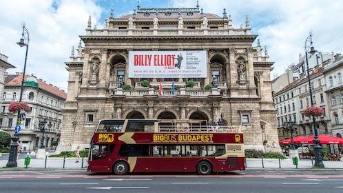 Hop on Hop off bus driving past a historical theater in Budapest