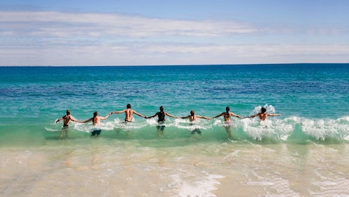 Group holding hands in the ocean on Rottnest Island