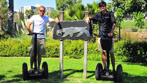 Segway riders posing near saber tooth sign in Los Angeles