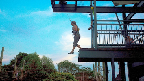 Woman jumping from a zipline platform at Megazip Park in Singapore