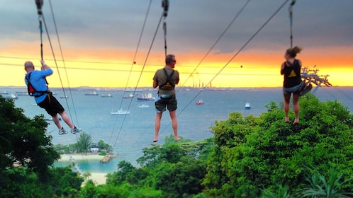 Three people zip lining at Megazip Park in Singapore