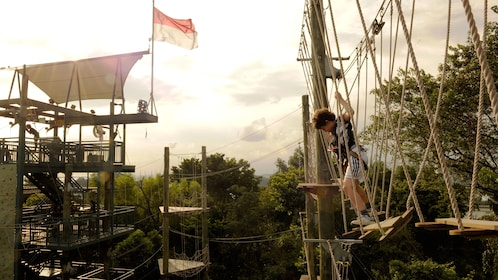 Woman looking down from a rope bridge at Megazip Park in Singapore