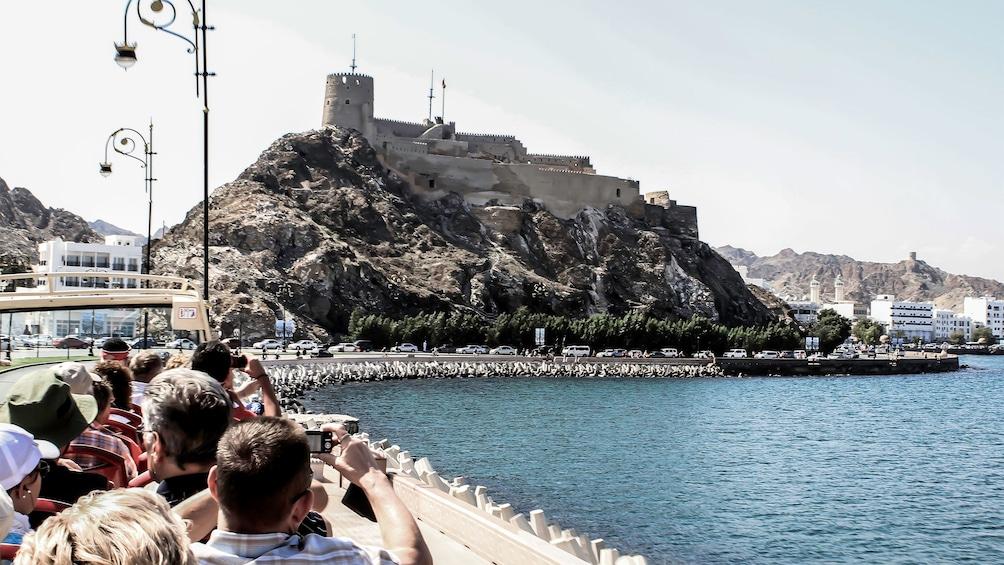 Foto 3 von 9 laden Hop-On Hop-Off bus passengers looking at Fort Al Jalali in the harbor of Muscat