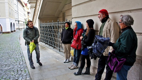 Tour guide with group on a sidewalk in Prague