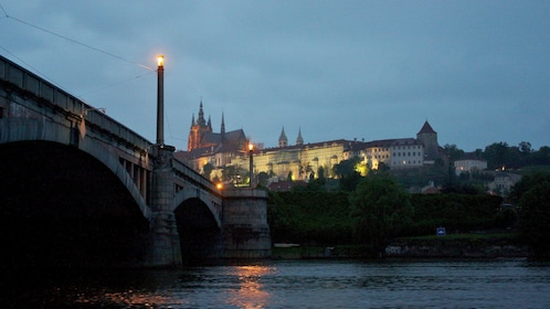 View of Prague at night from a boat on the the Vlatva river