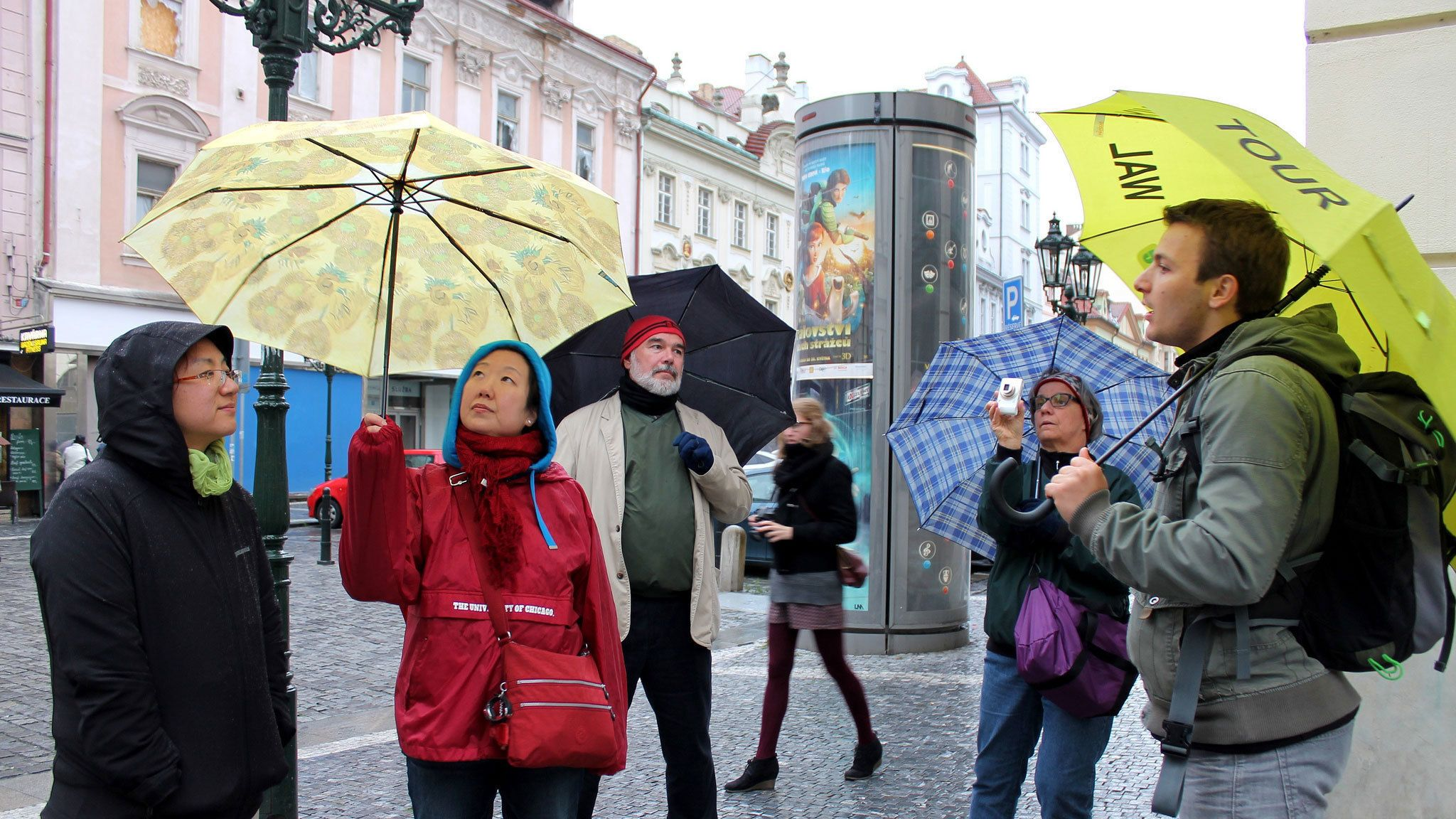 Tour group and guide with umbrellas on the street in Prague