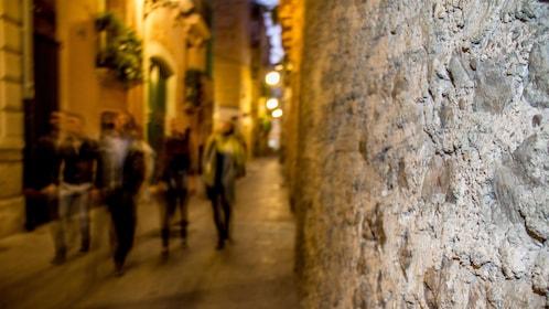 walking through a well lit stone alleyway in Spain