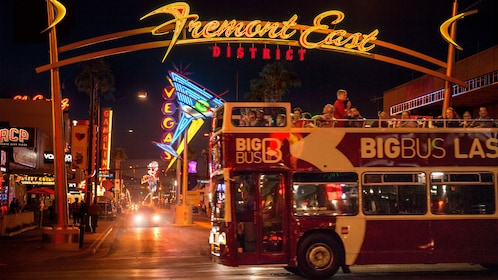double decker bus passing by the Fremont East District sign at night in Las Vegas