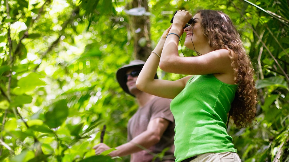 Show item 2 of 5. woman observing surroundings through binoculars in Grenada