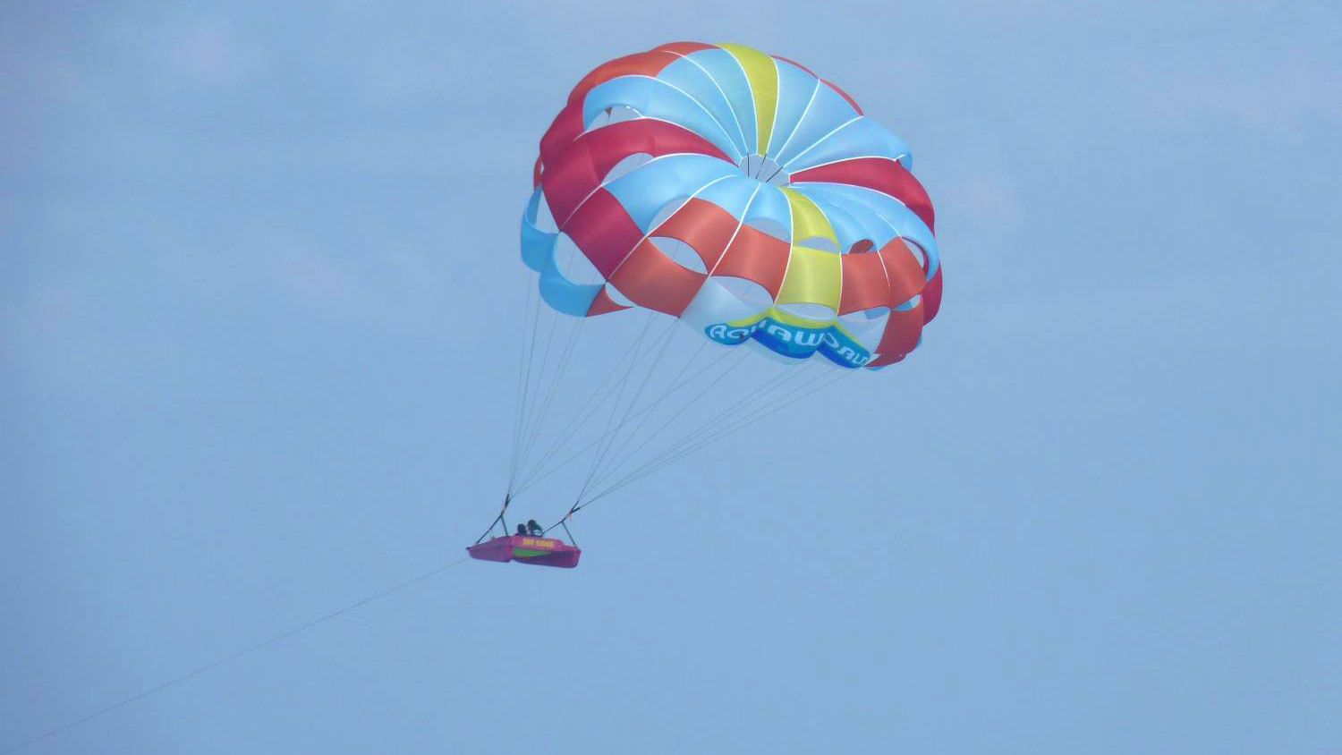 couple parasailing with a small raft in Key West