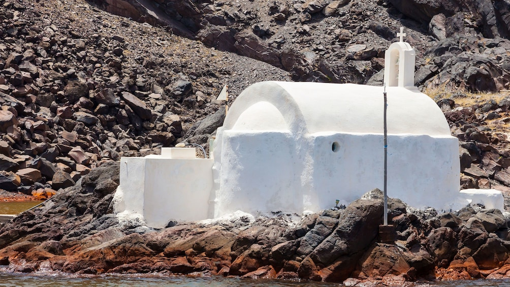 Show item 5 of 5. a small white church at the rocky coast in Santorini