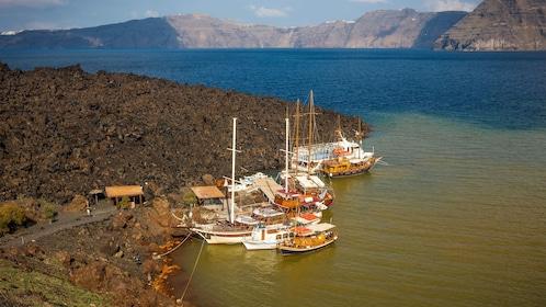 clustered boats along the coastline in Santorini