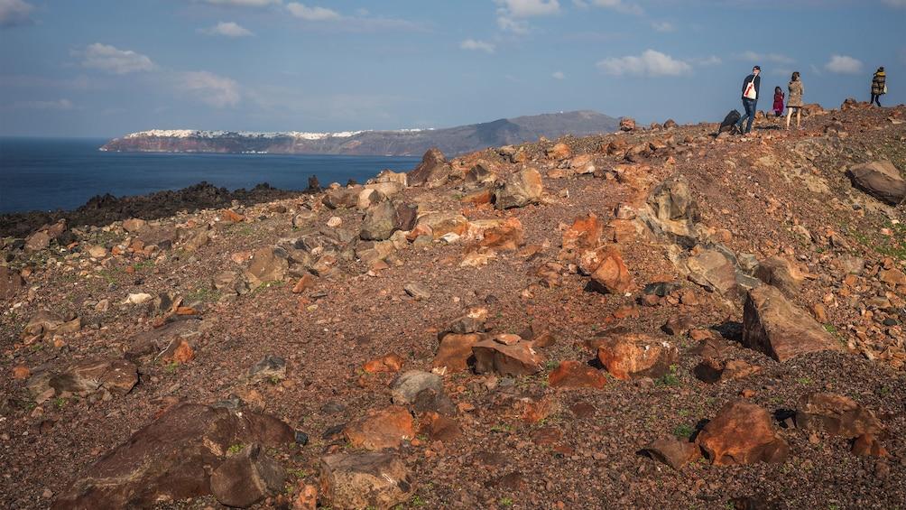 Show item 2 of 5. hiking up the rocky coastline in Santorini