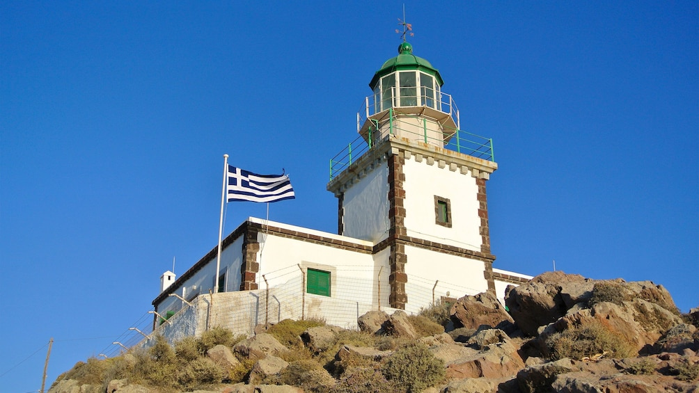 fenced lighthouse on top of the rocky hill in Santorini
