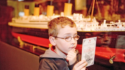 Boy reading an information card at the Titanic The Experience in Orlando