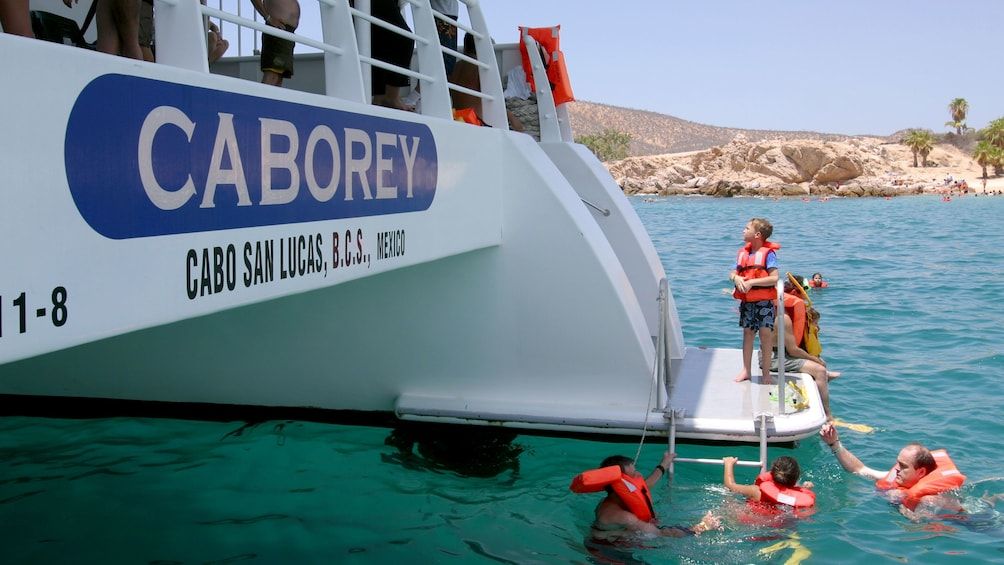 Show item 4 of 9. small group swimming near the passenger boat in Los Cabos