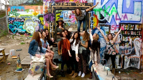 Group of women in various poses in front of graffiti in Austin Texas