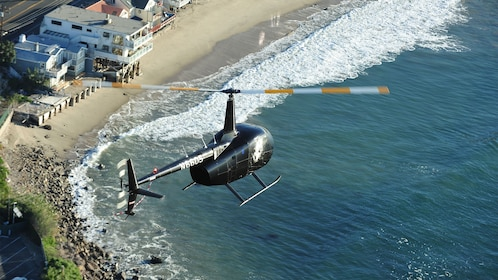 black helicopter soaring along the beachfront in Los Angeles