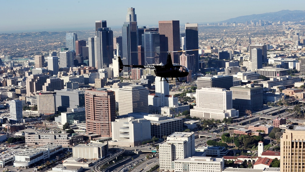 Show item 2 of 5. Black helicopter flying above the city of Los Angeles during the daytime
