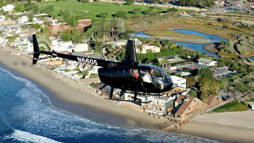 Show item 1 of 5. Aerial view of a black helicopter overlooking a body of water in Los Angeles