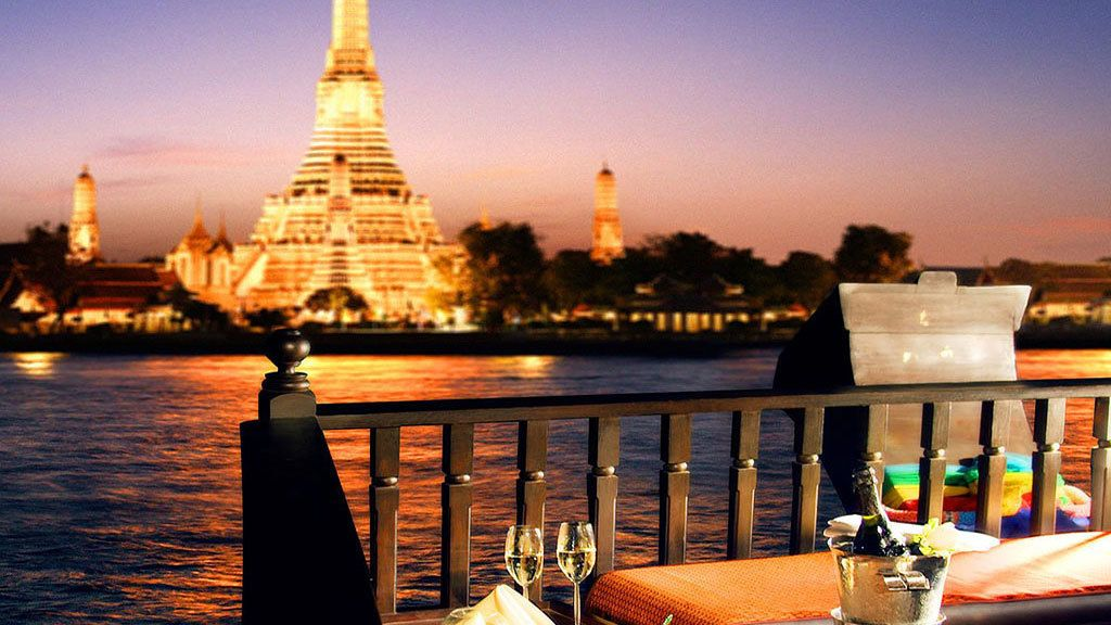 View of an illuminated temple on the banks of a river in Bangkok at sunset