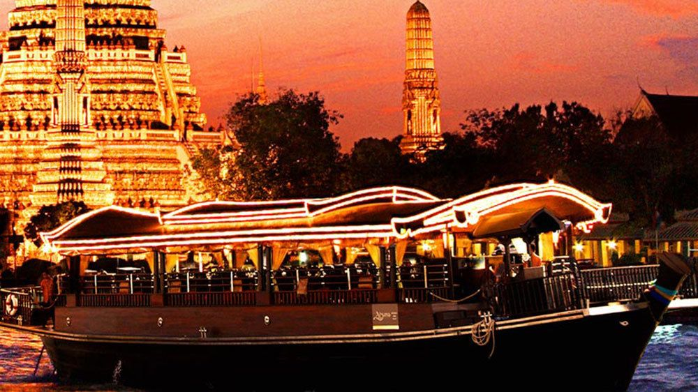 Dinner cruise boat sailing past an illuminated temple at sunset