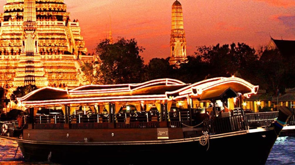 Show item 1 of 10. Dinner cruise boat sailing past an illuminated temple at sunset
