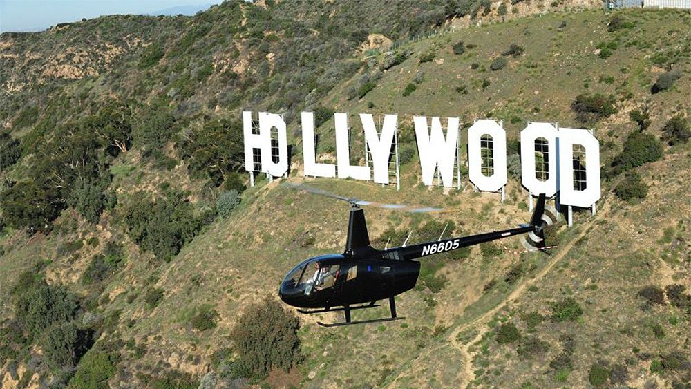 helicopter circling around the Hollywood sign on the hills in Los Angeles