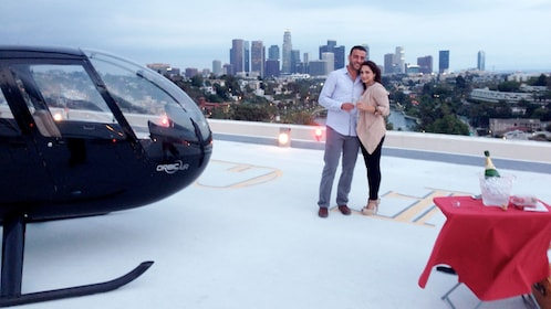 Couple taking a picture overlooking the city with the helicopter off to the left and dinning table off to the right