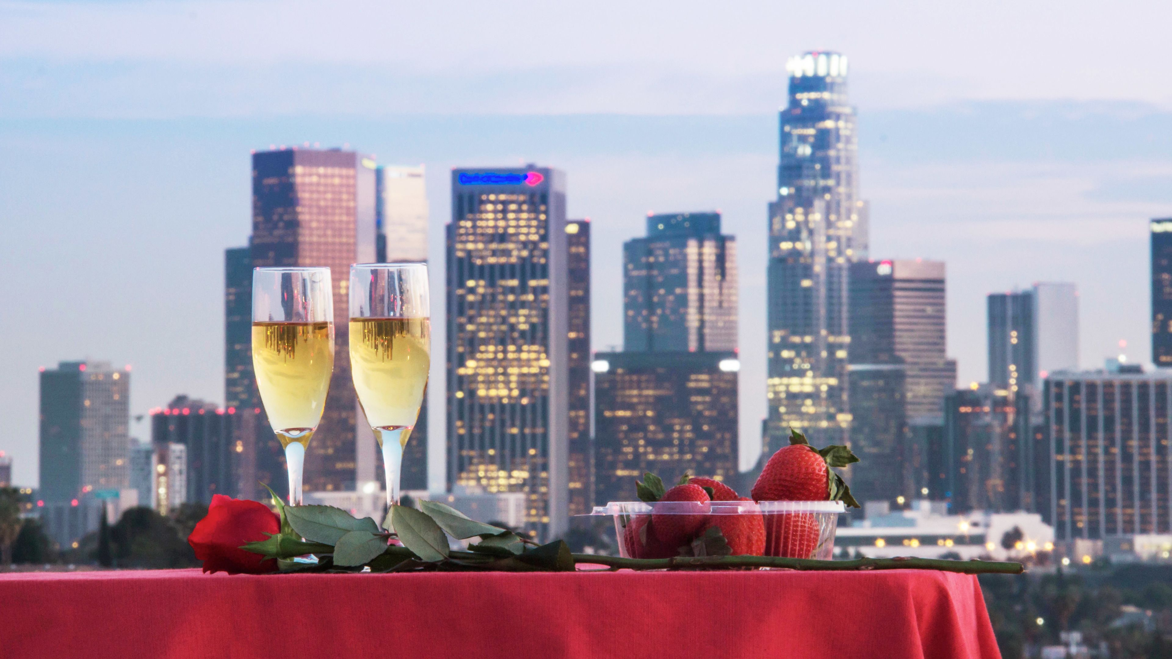 Two glasses of champagne and strawberries on a table overlooking the city in Los Angeles
