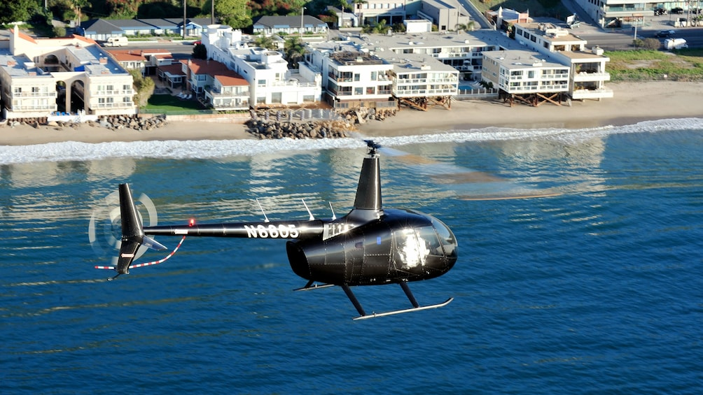 Show item 2 of 5. Black helicopter flying above Los Angeles water on a nice day
