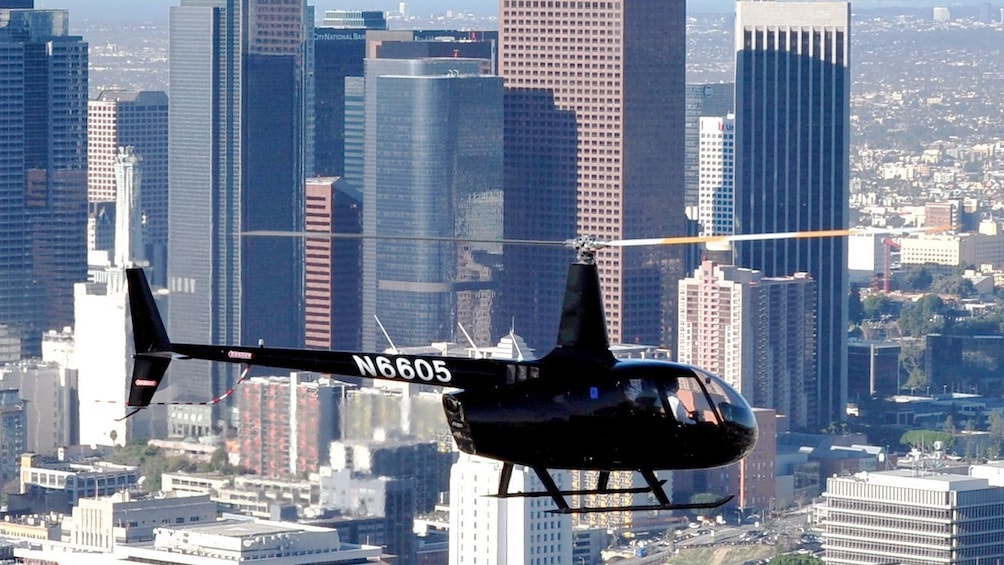 Show item 1 of 5. Black helicopter flying above Los Angeles city during the day