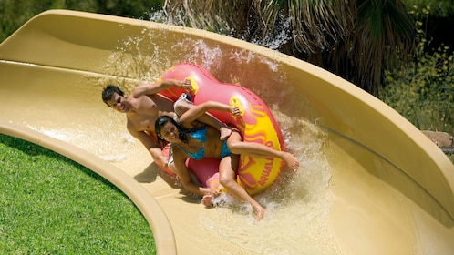 couple in an inflatable raft sliding down a curvy slide at the Aqualand Maspalomas in Spain