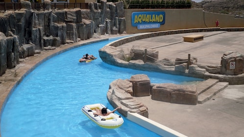 relaxing on flotation devices at the Aqualand Maspalomas in Spain