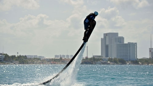 man performing a vertical climb with a water hoverboard in Cancun