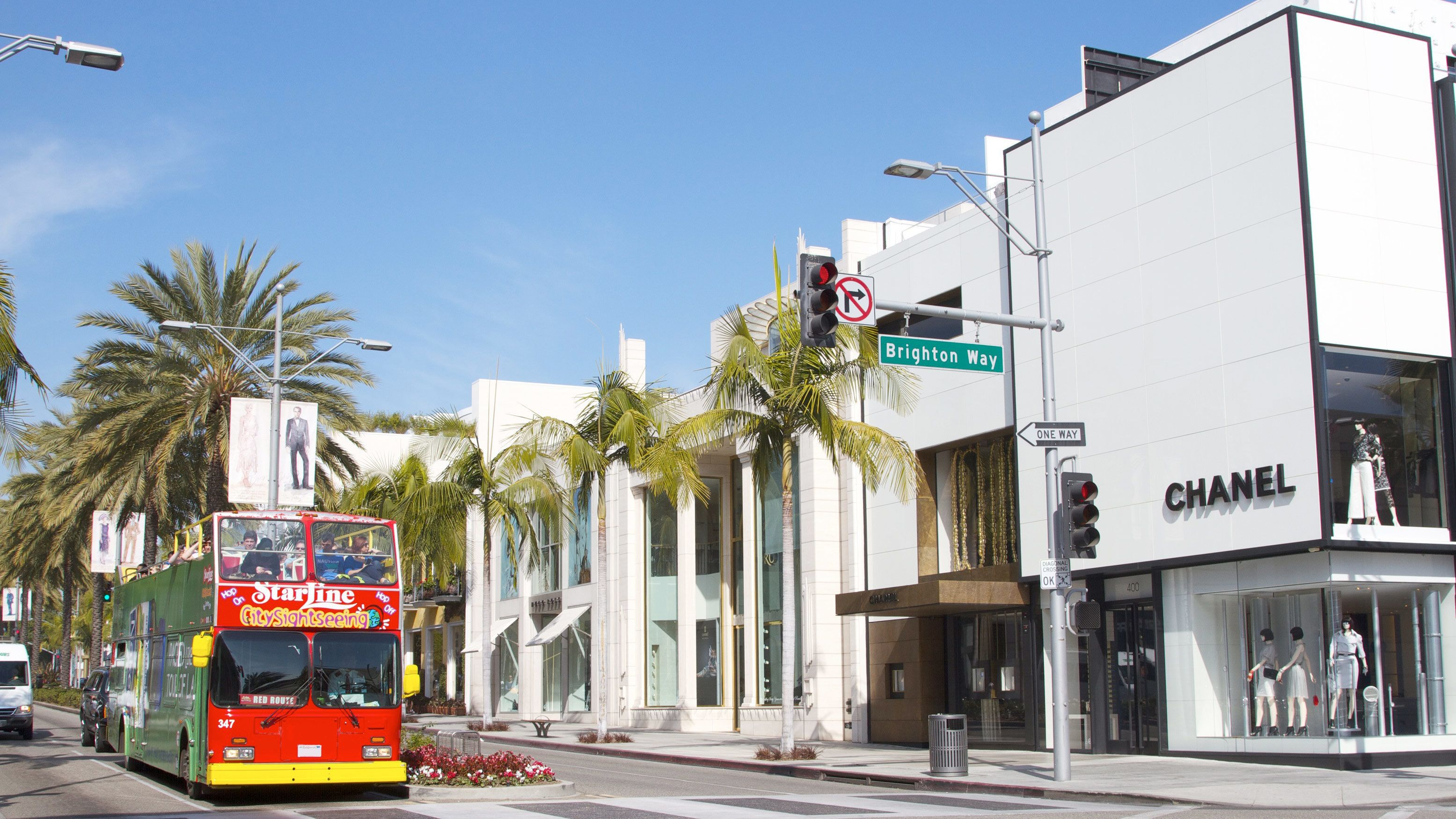 Double decker bus on the streets on Los Angeles in front of a Chanel store on a sunny day